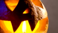 pumpkin head lit from within, her eyes, nose and mouth flickering candle light. All Saints Day will decorate this attribute video