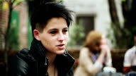 Punk girl smokes cigarettes during conversation, outdoors, steadicam shot video