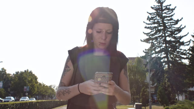 Punk girl typing a message while walking in city video