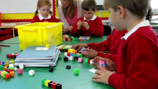 Pupils And Teacher Working With Coloured Blocks video