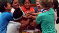 Pupils holding hands together and cheering in classroom video