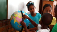 Pupils looking at the globe in classroom video