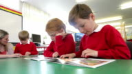 Pupils Reading At Table With Teacher Helping Them video