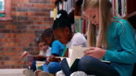 Pupils sitting in a row reading in library video