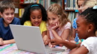 Pupils using the laptop together in library video