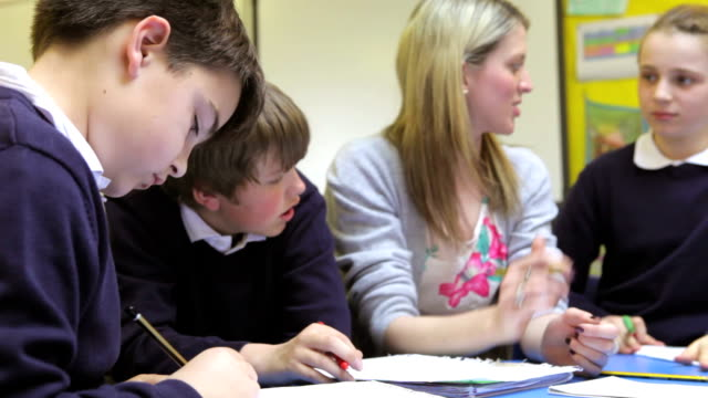 Pupils Working At Table With Teacher Helping Them video