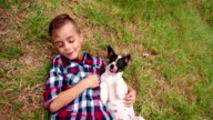Puppy licking little boy's face who is lying in grass video