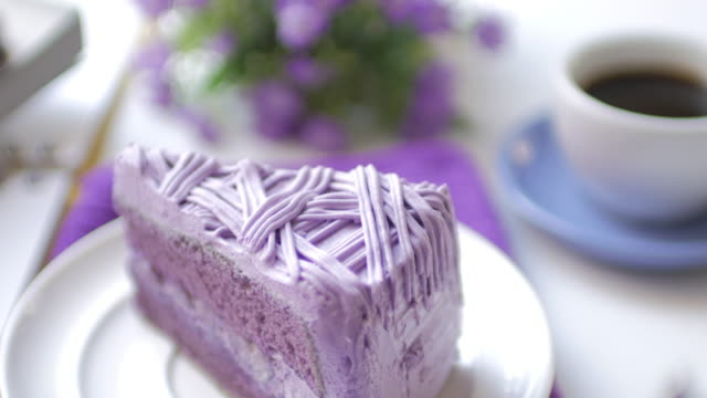 Purple taro cake with coffee on white table at coffee cafe , dolly shot movement video