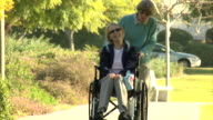 Pushing wheelchair in park HD video video