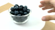 Put down bowl of fresh blueberries, bowl rotating, slow video