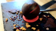 put on a chocolate sphere on a plate for decoration dessert. video