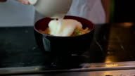Put soft-boiled egg on top of  fired rice. Slow motion. video