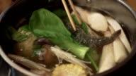 Put the raw food to sukiyaki Pot with hot water video