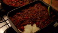 Putting meat sauce on chopped potatoes video