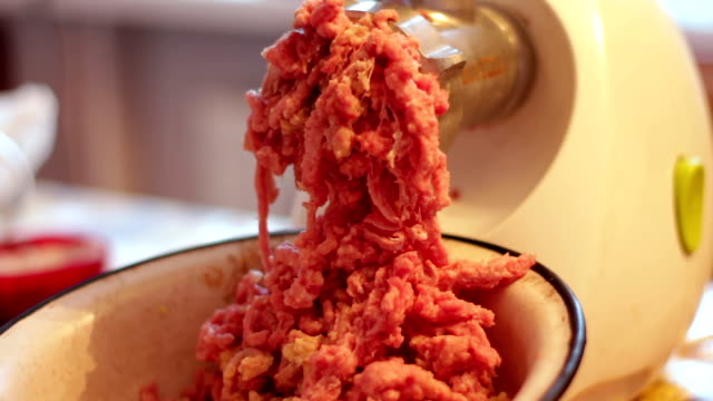 Putting minced meat and vegetable mixture through mincer at home at home video