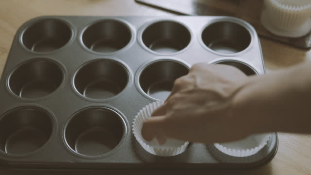 putting muffin cases into bake tin video