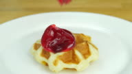 putting whipping cream and strawberry on top of the waffle. Front view. video