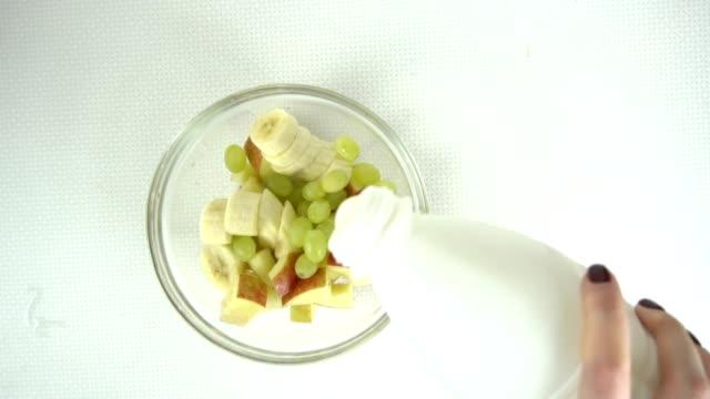 Putting yogurt into fruit salad, slow motion video