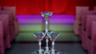 pyramid of glasses, martini with cherry juicy inside. is on the table, in the center of the ceremonial hall, perhaps a wedding or anniversary, at the edges of the rows of chairs video
