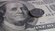 Quarter coin spinning over hundred dollars bill. Currency. Finance. Money. video