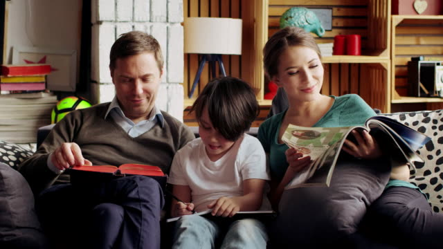 A quiet family night, parents read books, and the boy learns lessons video