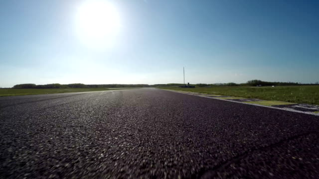 FPV LOW ANGLE: Racecar driving fast competing on racetrack on sunny day video