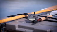 Rack focus of a fly fishing rod resting in a canoe during a fishing trip video