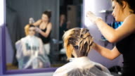 A radical change of hair color. Attractive blonde woman in a beauty salon video