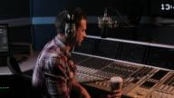 DJ radio presenter operating controls in studio video