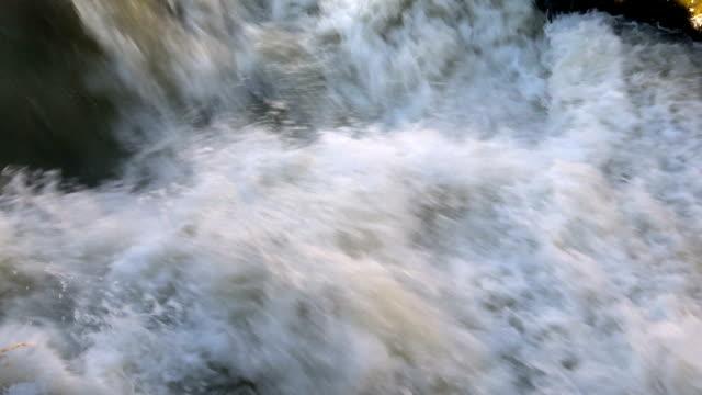 Raging clean fresh mountain river flowing between rocks in slow notion video