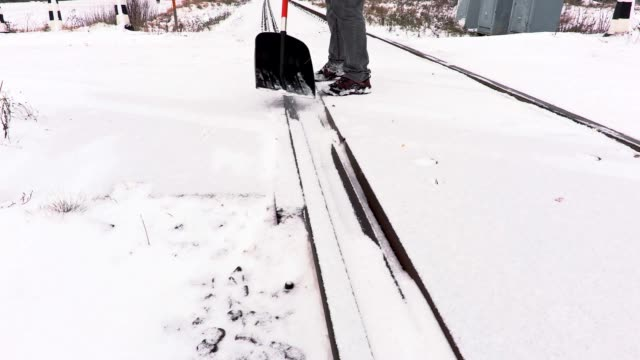 Railroad employee clean snow from the railway crossing video