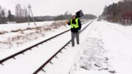 Railroad employee with snow shovel on railway video