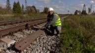 Railroad worker talking on smart phone near the rails video