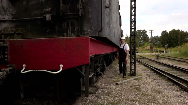 Railway employee climbs up on locomotive video
