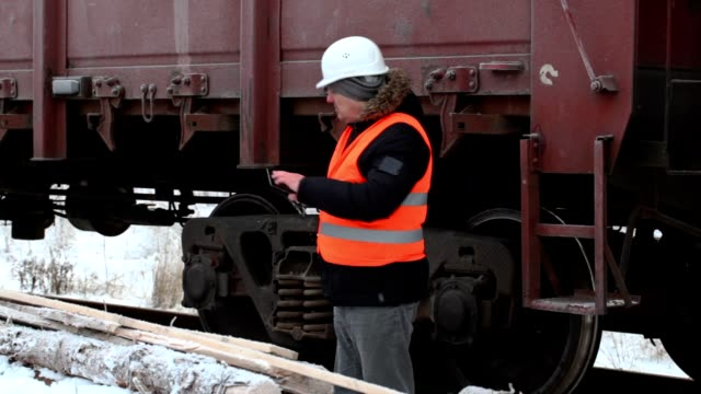 Railway officer take picture near freight wagons video