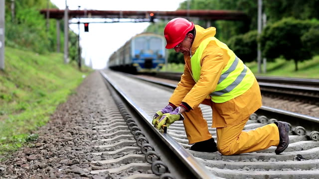 Railway worker in yellow uniform with level measuring instrument on railway line video