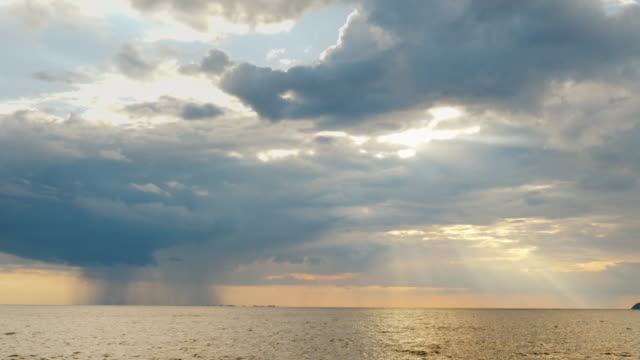 A rain cloud with rain over the sea and a setting sun with beautiful rays. Amazing sunset over the sea video