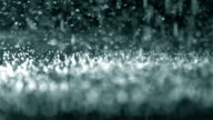 Rain drops falling into ground, slow motion video