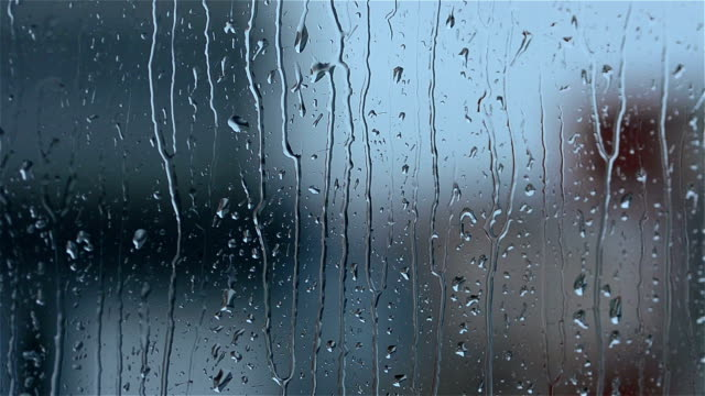 Rain drops running down a window pane video