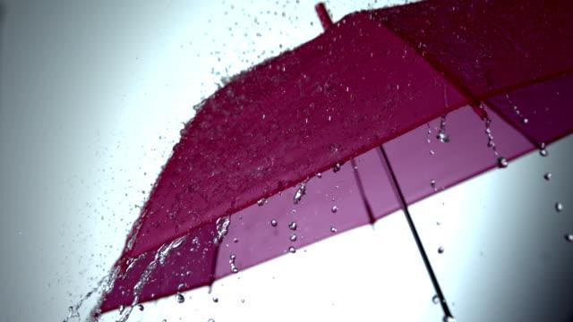 Rain falling on pink umbrella video