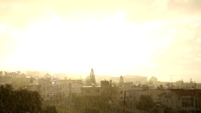 Rain falls against backdrop of village and trees video