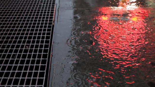 rain on sidewalk with grate and reflected neon light video