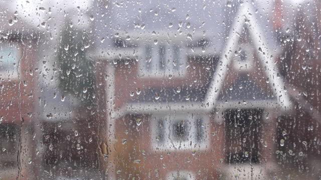 Rain on suburban window. Defocused house. video