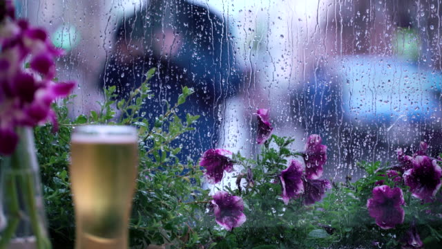 Rain outside the window of the café. A glass of beer. Raindrops on window glass, beautiful bokeh behind a wet city window. Abstract silhouettes of people walking under umbrellas. Concept of lifestyle of modern city. Intentional blurring of backgrounds in video