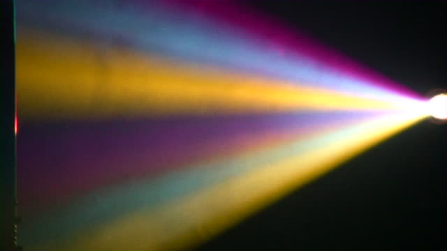 Rainbow light beams from a prism on black background video