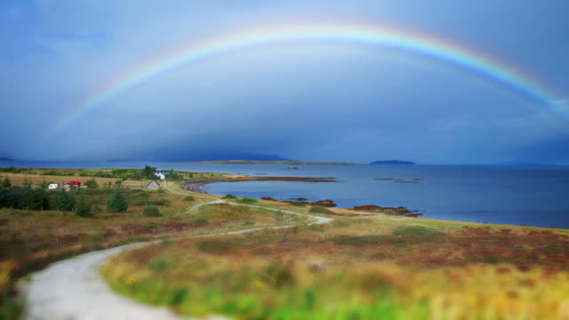 Rainbow over village in Scotland time lapse video