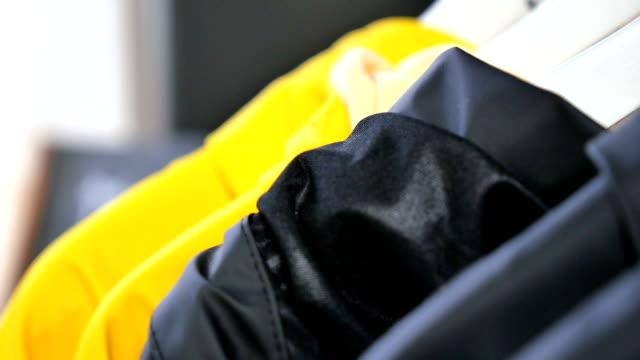 Raincoats on rack outside shop video