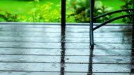 Raindrops falling on the boards of porch. Slider shot video