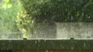 MACRO SLOW MOTION: Raindrops falling on the ground and splashing around and glittering in the morning sun video