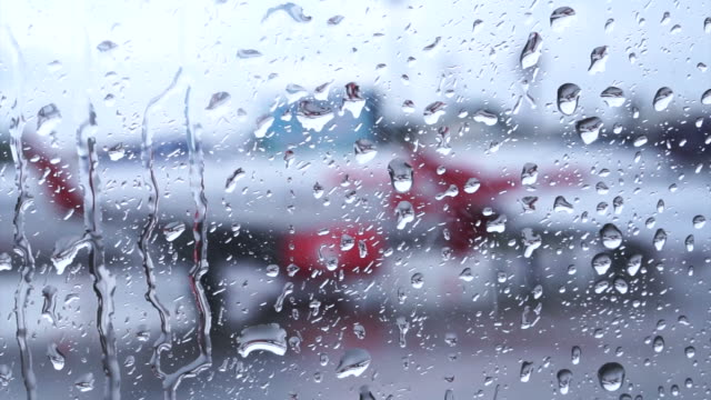 Raindrops on the air plane window with blur airport outside video